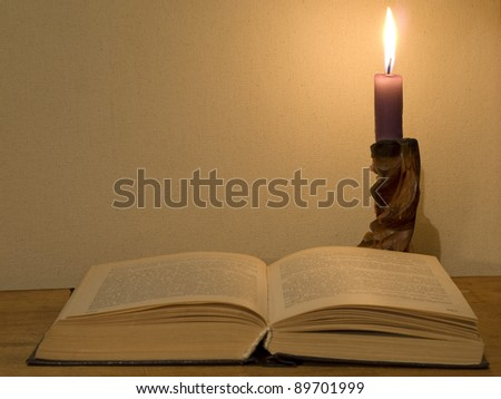Old open book and  glowing candle on a wooden table. - stock photo