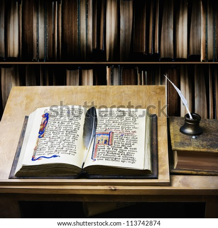 old open book and quill pen to write on the table - stock photo