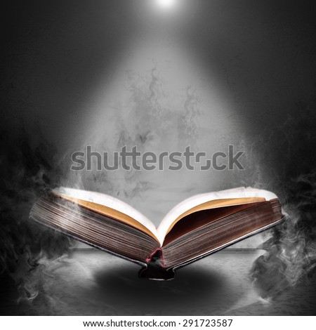 Old open book in the magical smoke on a gray concrete grunge background