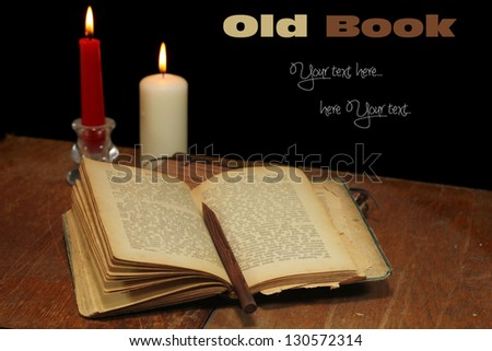Old open book on a wooden table. - stock photo