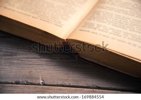 Old open book on wooden background close-up