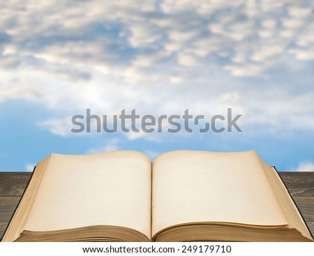 old open book with blank pages sky background out of focus
