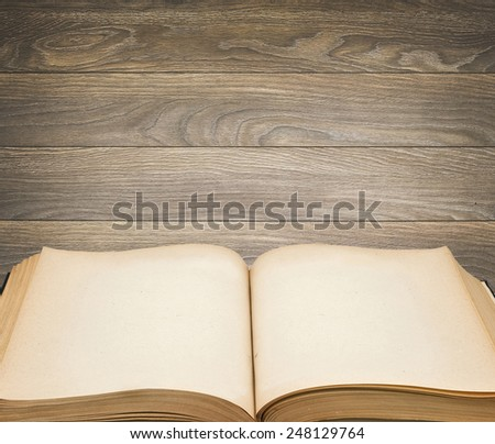 old open book with blank pages with a wooden background