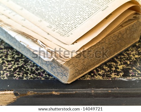 Old open book with closed book at the white table