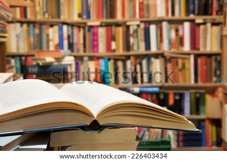 Old open book with library background - stock photo