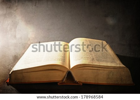 Old open book with magic light from left side on a dark abstract background