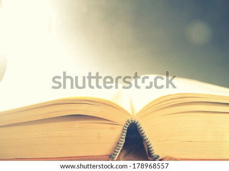 Old open book with magic light on a bright abstract background