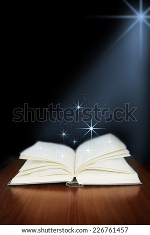 Old open book with magic light  on wood planks and dark abstract background