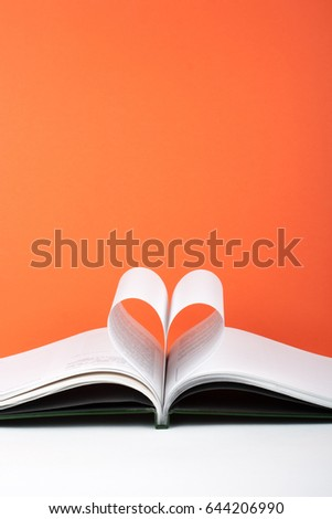 Old open hardback book, page decorate into a heart shape for love in Valentine's. love with open book heart