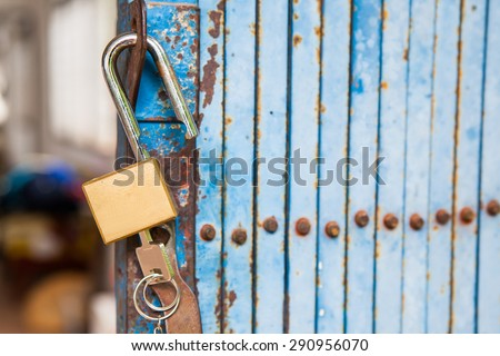 Old open padlock and key with old steel door - stock photo