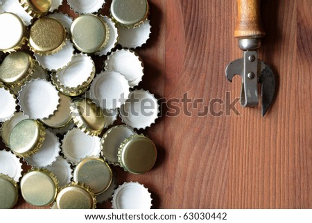 Old opener near lot of bottle caps on wooden background - stock photo