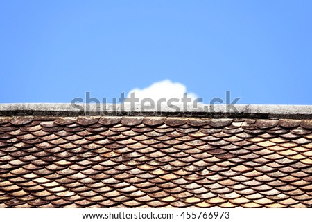 old orange grunge thai style cray roof wiht blue sky and clouds background,select focus with shallow depth of field:ideal use for background