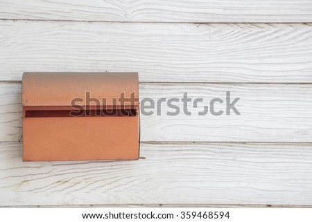 Old orange postbox on wooden wall. - stock photo