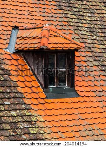 Old orange roof with retro dormer window - stock photo