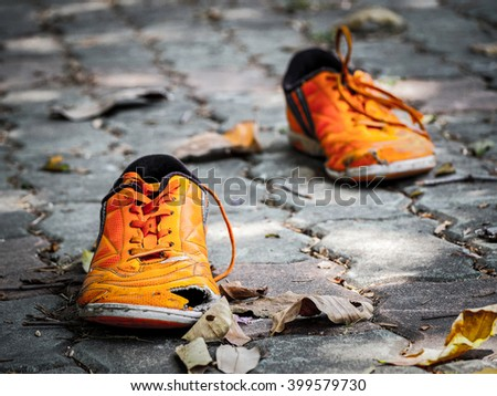 Old orange running shoes with holes, selective focus - stock photo