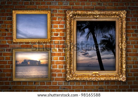 Old ornate golden frames hanging on a brick wall with a window into paradise. - stock photo