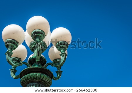 Old ornate lightest with multiple lights against  a bright blue sky - stock photo