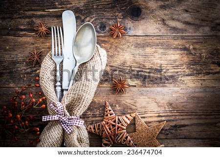Old ornate wooden board with cutlery. - stock photo