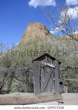 old outhouse by mountains - stock photo