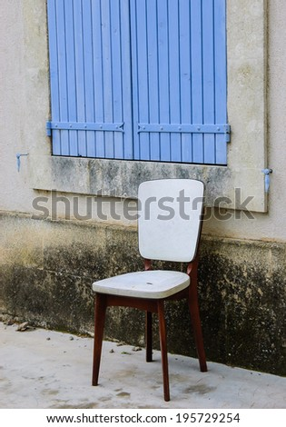 Old padded white leather chair standing near the window with closed wooden shutters outside of  the old house with stucco wall. Provence, France. - stock photo