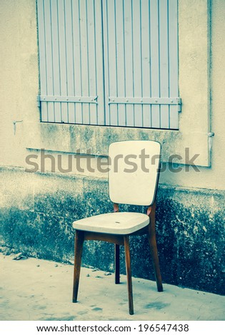 Old padded white leather chair standing near the window with closed wooden shutters outside of  the old house with stucco wall. Provence, France. Aged photo. - stock photo