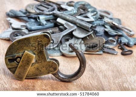Old padlock and heap of keys on wood - stock photo