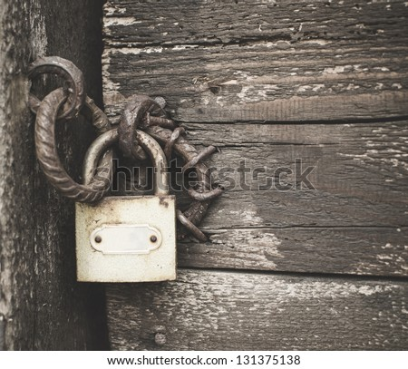Old padlock on a wooden door - stock photo