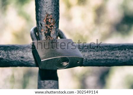Old padlock on iron bars - stock photo