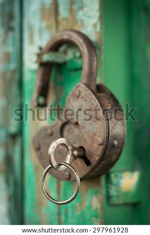old padlock with key on a green wooden wall - stock photo