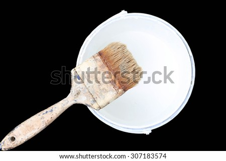 Old paint brush rest on top of  paint tin isolated in black background - stock photo
