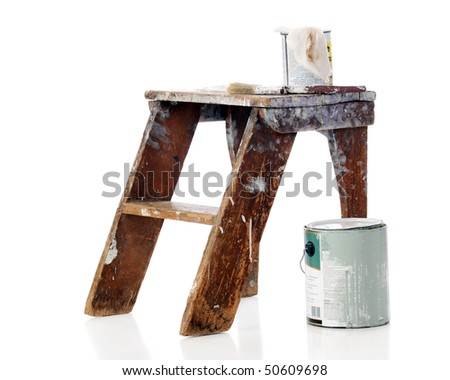 Old paint buckets, a brush and rag on a well-used step stool.  Isolated on white.