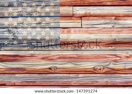 Old Painted American Flag on Dark Wooden Fence  - stock photo