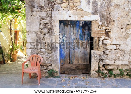 Old painted blue door on the ancient stone wall in greek village, Crete, Greece
