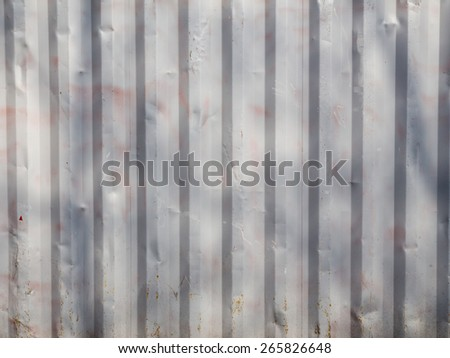 old painted metal corrugating wall with dents and stains - stock photo