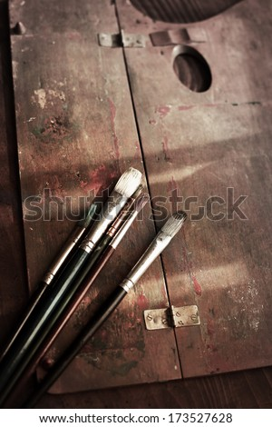 Old painting brushes and a wooden palette on an old painters desk.  - stock photo