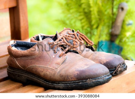 Old pair of gardening shoes on a bench - stock photo