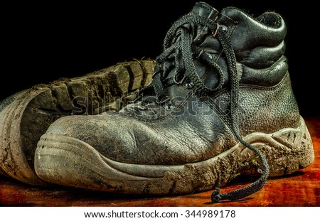 Old pair of used dirty work boots covered in dry mud.With copy space - stock photo