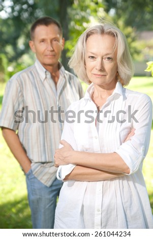 Old pair posing for camera in park - stock photo
