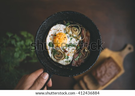 old pan in hand. fried egg, bacon, onion rings, parsley - tasty Breakfast or snack.  On a dark wooden out of focus table. On the table there is bread and parsley. Top view - stock photo