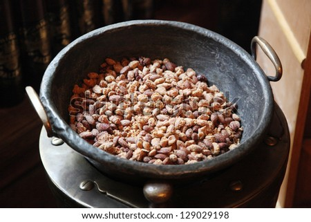 old pan with peanuts - stock photo