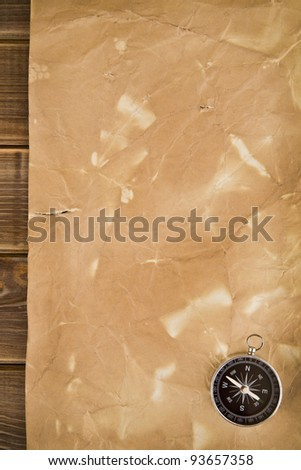old paper and compass on a wooden background - stock photo