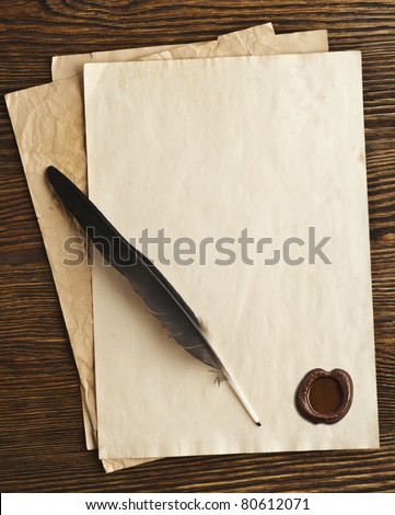 old paper and feather with a wax seal on a wooden background