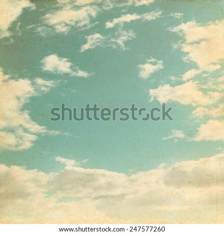 Old paper background with blue sky and white clouds in grunge style.