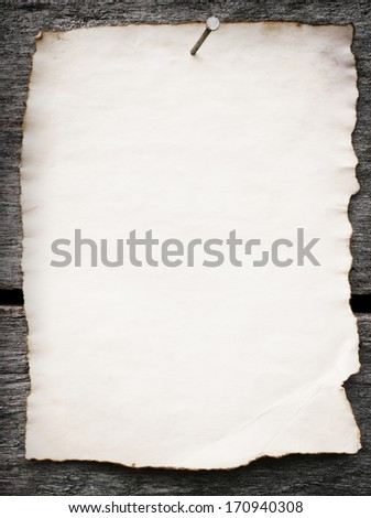 Old paper nailed to a grunge wooden background - stock photo