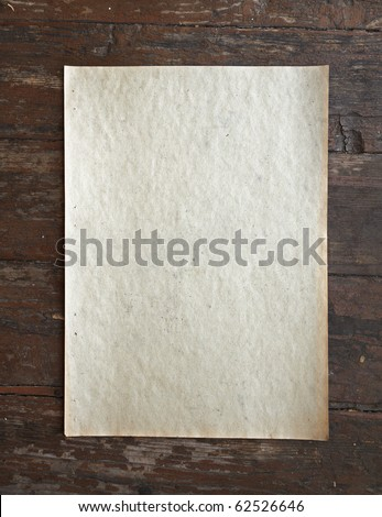 old paper on dirty wooden background - stock photo