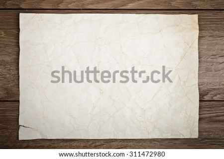 Old paper on wooden table - stock photo