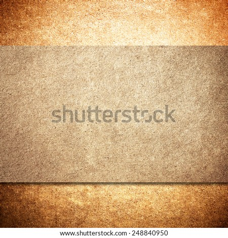 Old paper or cardboard over yellow or orange concrete wall background - stock photo