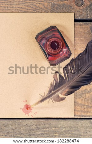 old paper, pen, feather and ink on wooden table - stock photo