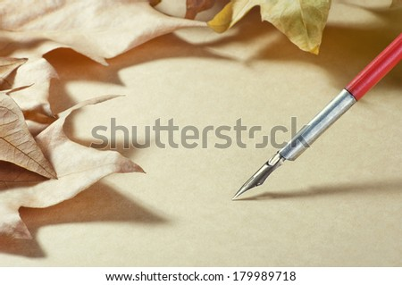 old paper pen fountain and maple foliage - stock photo