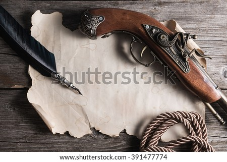 old paper ,pistol and  fountain pen on the wooden board - stock photo